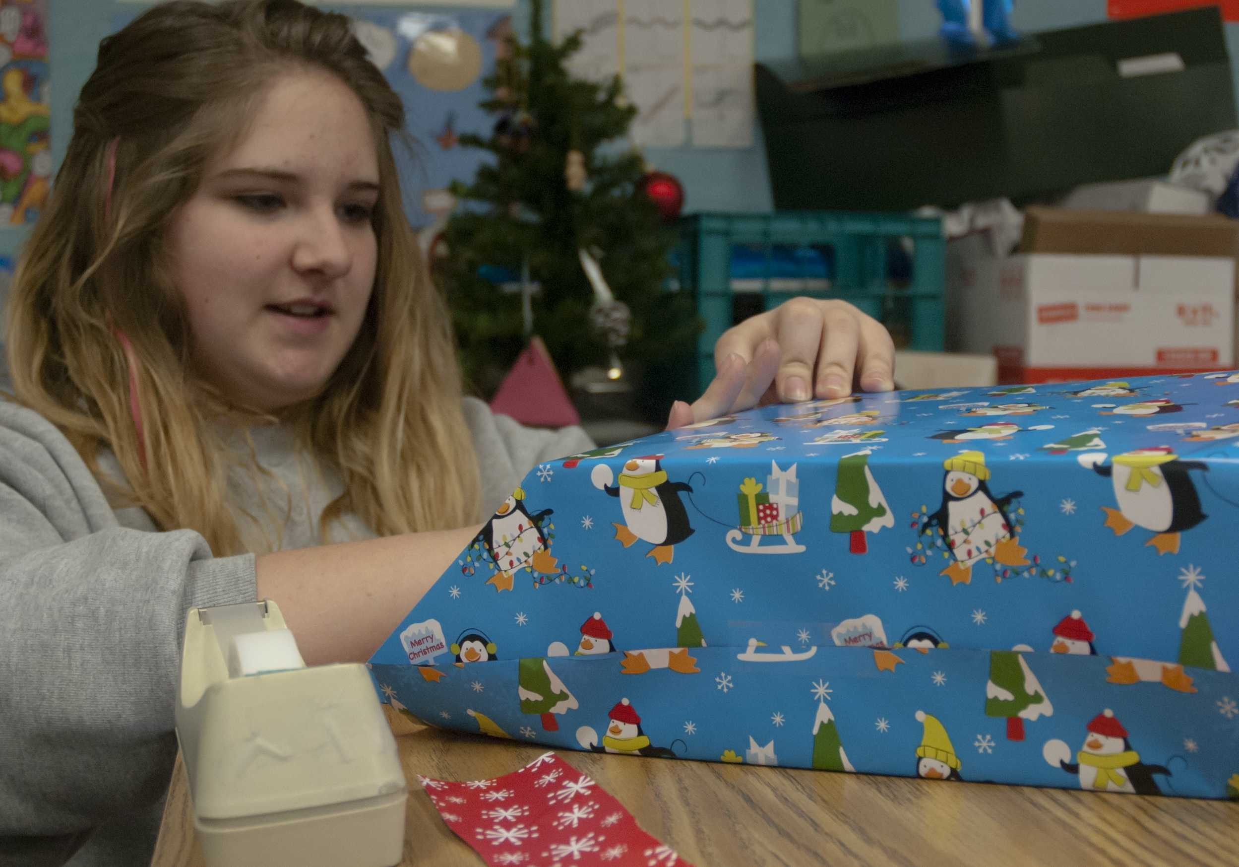 Sophomore Hannah White wraps a gift on Dec. 4 in preparation for Adopt-a-Tot. Fourth hour classes are sponsoring Headstart program families to provide them and their children with a Christmas celebration. The children will visit SMNW on Dec. 7 for the annual Adopt-a-Tot celebration, where they will get to open some of their gifts earlier. Photo by Clara Davison.