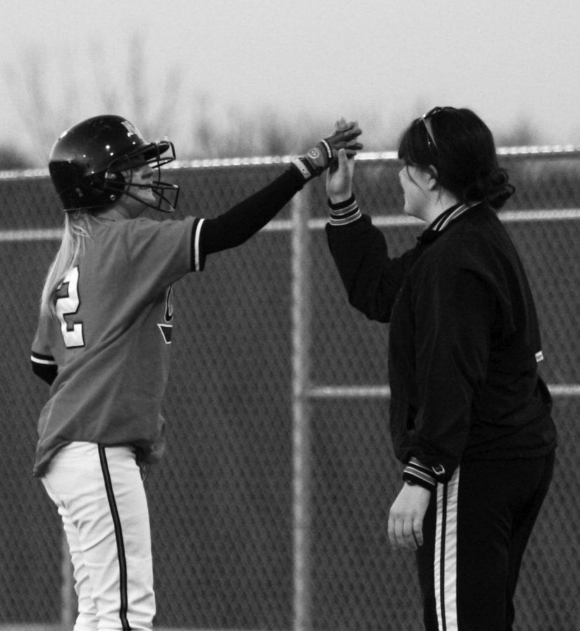 Coach Lindsay Kincaid gives player Loryn Goebel a highfive.