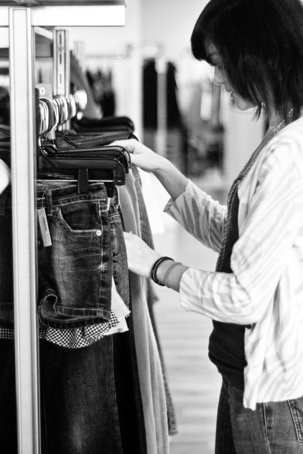 """Junior Haylee Slocum looks through clothes at Ditto consignment store in Overland Park. """"I just wear what I feel like. And whatever feels comfortable or looks cute that day. I don't really have a set style,"""" Slocum said."""