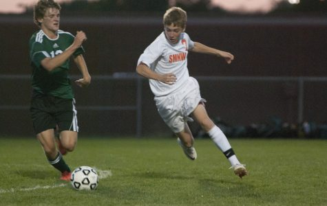 Sophomore Ethan Bowman dribbles the ball past SM South player Griffin Zeller at SMAC on Sept. 18. The Cougars won the game 4-1. Photo by Clara Davison.