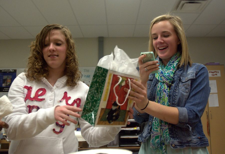 Interact Club executive board member senior Caitlin Beatty passes a gift to sophomore Anna Benoit while reading directions for a White Elephant gift exchange game. Members of Interact Club celebrated the holiday season and the end of first semester with games and food. Interact Club is Rotary International's youth service organization, and the group meets every other Wednesday morning in room 202 at 7:10. Photo by Clara Davison