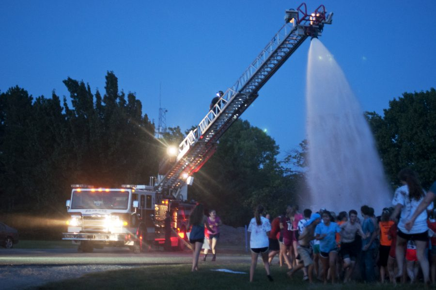 Students rush towards the spray of water coming from the water truck at the end of Muckfest. The firetruck hosed off the students so that they could rinse off some of the muck before driving home.