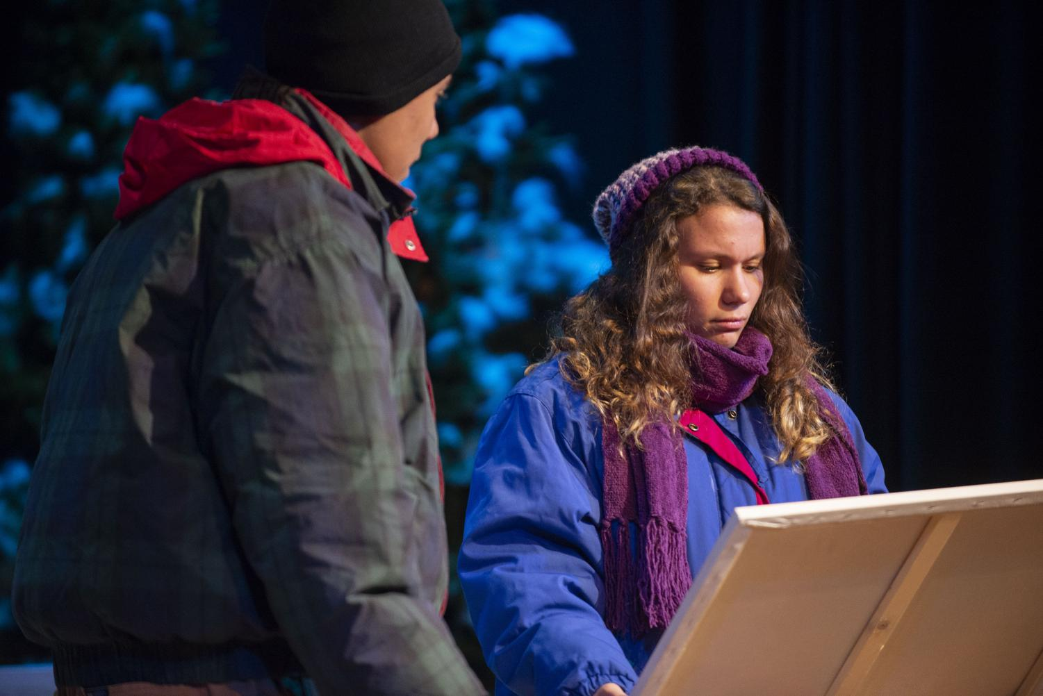 Under their 12 layers of winter clothes and the hot stage lights, junior Natalie Hole and senior Christian Anderson examine a painting during a dress rehearsal of