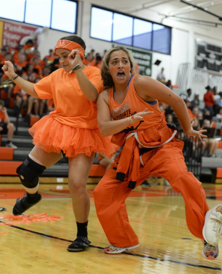 Juniors Payton Smith and Rylee Garrett dance in the junior skit during the bonfire assembly on Aug. 29 in the Main Gym.