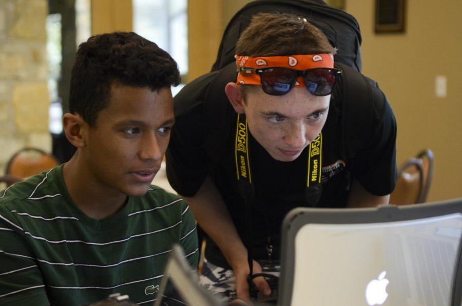 Junior Dylan Mitchell helps freshman Ben Nash edit photos.