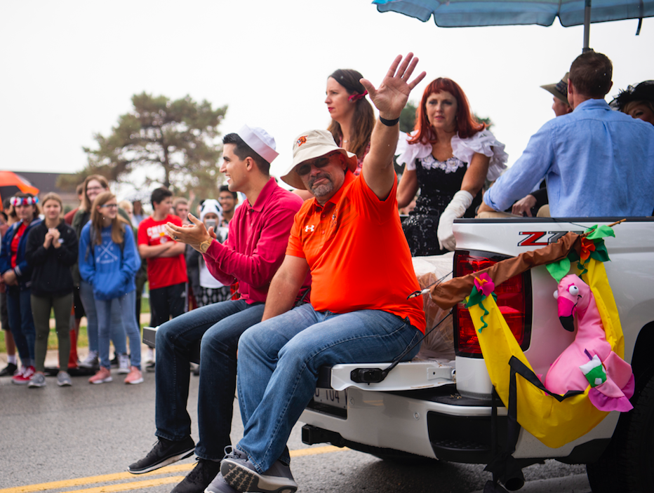 On the back of the office truck, Athletic Director Angelo Giacalone waves the students lining 67th street Oct 5.